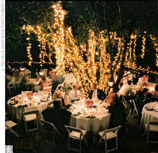 "Tamara and Eric's reception was held at a rustic mountain cabin with a wooden deck outside and a real tree planted right in the middle of the deck. Twinkling lights were wrapped around the tree, which Tamara says gave the setting ""an intimate fairy-tale feeling,"" and tiny antique lanterns dangled from a few of the branches."