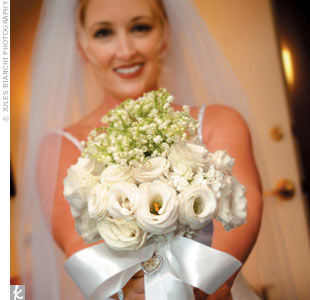 Tiffani's all-white bouquet included lisianthus, garden roses, and lilies of the valley tied with white satin ribbon and a four-leaf clover heart shaped pendant (in honor of her Irish heritage).