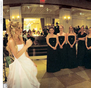 The nine bridesmaids wore black satin A-line dresses by Nicole Miller.