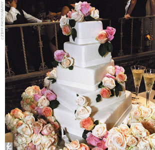 Following a gourmet feast, approved by the successful restaurateur, the couple cut a show-stopping five-tier yellow genoise wedding cake with white icing and decorated with various shades of pale roses. Tuxedo chocolate-covered strawberries were served with the rich wedding cake.