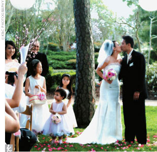 Diemmai and Huy exchanged vows in a Western wedding ceremony at the Japanese Garden in Hermann Park. Guests sat in a clearing near the teahouse, and white hanging lanterns and cherry blossom arrangements demarcated the altar.