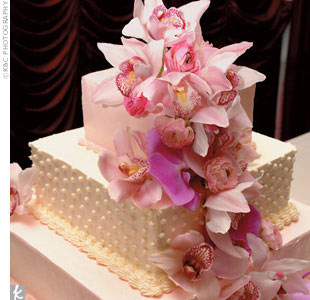 At the center of Diemmai and Huy's reception, the wedding cake held court -- a three-tier square strawberry cheesecake frosted in layers of white and pink, and adorned with a cascade of orchids.