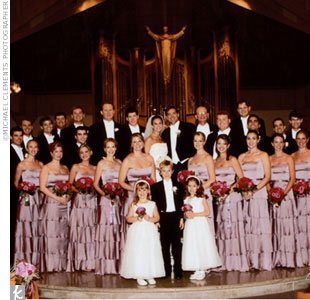 Jackie's bridesmaids wore mauve strapless charmeuse dresses with tiered A-line skirts by Lazaro. They carried round bouquets with purple maritime roses, deeper magenta poison roses, royal majesty roses, scarlet mini roses, and bupleurem.