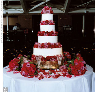 Jackie and Cole's cake featured four tiers of white vanilla cream cake separated by bundles of red, magenta, and deep pink roses.
