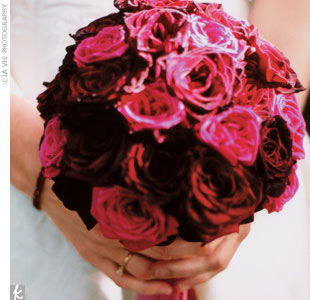 The bride's bouquet included a mix of dark red and pink roses wrapped in vintage-pink silk ribbon and accented with thinner burgundy ribbons.
