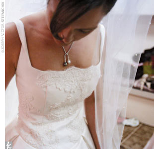 Nicole honored her mother by accenting her own wedding gown with straight lace restored from her mother's 1969 gown. Nicole designed the white silk satin gown in collaboration with dressmaker Judy Shannon who did all of the restoration work on the lace from her mother's gown and handcrafted the updated gown, veil, and tiara.