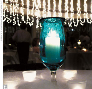 The personal flair of the bride's father also dramatized the reception space. He had transparent aqua glass candleholders made, which each held a white pillar candle, along with frosted votives to surround each piece and rest together on spun glass.