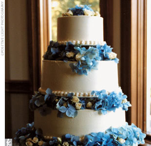 The four-tier white wedding cake with raspberry filling was accented with blue hydrangeas and cream spray roses between each tier.