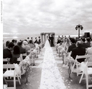 """Since many of their 105 guests were traveling from far away, Lisa and Eric planned their wedding for a Friday night. """"We wanted them to have Saturday and Sunday to relax on the beach with us,"""" says Lisa. """"We even sent our save-the-dates on bookmarks so that people would bring books with them to read on the beach.""""  But planning a beach wedding brin ..."""