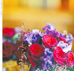 Red roses and purple flowers added vibrant color to Margaret and Alex's theatre-inspired celebration.