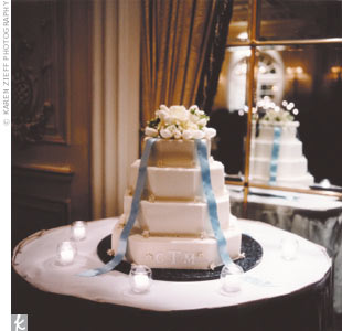 Christine and Mark's guests enjoyed a four-tier chocolate cake with white frosting, adorned with a bouquet and a silver-blue ribbon.