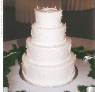 Amy and Shawn cut a white frosted confection topped with sugar glitter and sugar snowflakes.