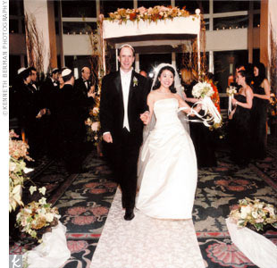 Cathy and David's celebration was a black-tie event: The bride wore a classic ivory strapless gown designed by Peter Langner. Her bridesmaids wore sleek, black strapless dresses. And the groom and his party wore traditional tuxedos.