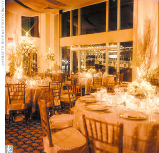 At Cathy and David's reception, columns were transformed into trees and centerpieces arched far toward the ceiling. Tall iron topiaries topped with candles featured overflowing, garden-inspired arrangements of branches, autumnal foliage, and berries. Low, lush arrangements of roses, dahlias, hydrangea, and calla lilies, along with grapes, pears, an ...