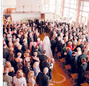The Christian wedding ceremony was held in the lodge's Great Room, which, with its soaring ceilings and tall glass windows, has a cathedral-like sense of grandeur. On her way down the aisle, Suzanne's cathedral-length wedding veil got snagged on an air-conditioning vent, causing a brief de-tangling pause in the procession.