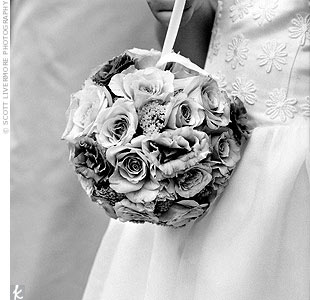 The flower girl carried a pomander of white, cream, pink, Oceania, soft yellow, and lavender roses, the same flowers as were in the bride's bouquet.