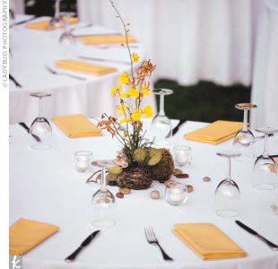 The tables were decorated with centerpieces of moss orbs wrapped in copper wire, and river rocks, candles, twigs, and orchids.