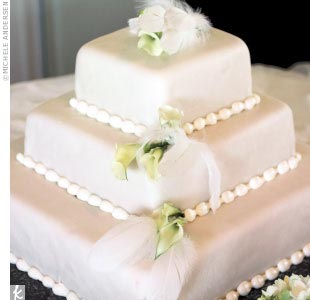 Mykle and Glen's cake was a three-tier ivory cake featuring lemon filling, ivory fondant, and calla lily and feather embellishments.