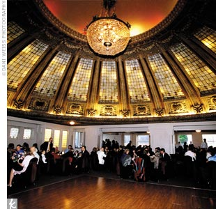 The reception was held at the Dome Room in downtown Seattle. The ballroom got a chic autumnal makeover with hurricane-lamp centerpieces, tons of candlelight, and fresh fruit accents.