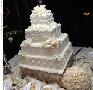 The bride's cake was a four-tier white cake adorned with the couple's monogram and white roses.