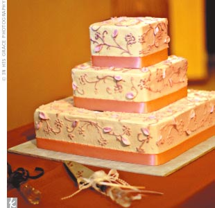 The wedding cake was a three-tiered square cake, filled with chocolate and white cake with dulce de leche filling, and iced with buttercream in a pink lace design.