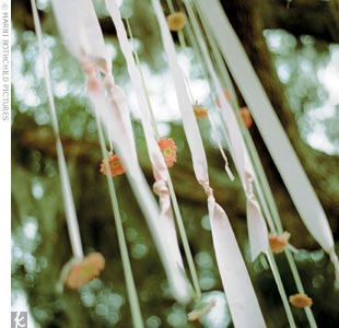 There was no formal altar to mark the outdoor spot where the couple exchanged vows, so the wedding planners hung ribbons with gerbera daisies attached from an old oak tree overhead.
