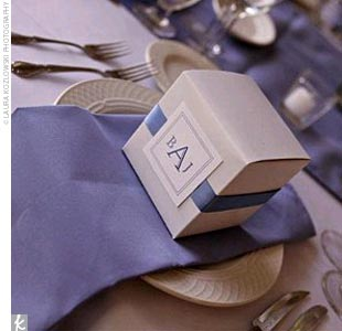 One of the key style motifs of the day was a monogram and ribbon theme. Brooke had spotted CD cases on TheKnot.com that were wrapped in ribbon with a square monogram closure. She incorporated a similar look into the invitations, programs, welcome baskets, centerpiece vases, and the favors. The favors themselves were tulip bulbs -- a nod to the brid ...
