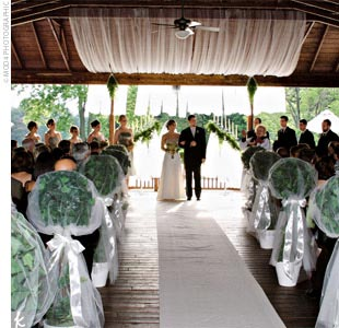 Amy and Josh exchanged vows under a decorated pavilion on the first hole of the golf course at The Pine Knob Mansion and Carriage House, framed by a background of fragrant pine trees.