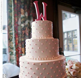 "Katie and John chose to slice into a three-tier cake with buttercream icing decorated with pink dots. The confection was topped off with a ""W"" cake topper."