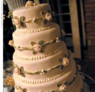 "The five-tier cake was covered in white fondant, small gold and green vines, and light pink roses and pearls. ""Our baker named it 'The Lani' and said she'd never made such a beautiful cake,"" says Lani."