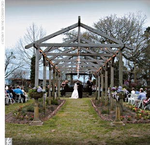 Lani and Matt fell in love with the rustic cottages and gorgeous greens of Elmwood Gardens. The bride walked under a wooden archway draped with twinkling lights to the light-strewn gazebo altar.