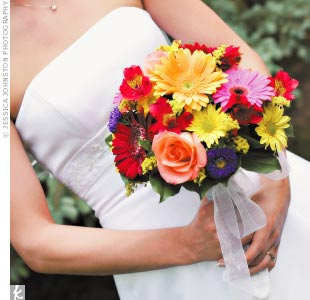 Aly accented her simple white A-line gown with a mix of vividly hued roses, alstroemeria, gerbera daisies, and mums.
