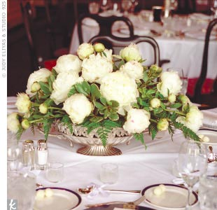 On Harry and Holly's reception tables, low silver bowls of peonies were mixed with tall arrangements of French tulips that complemented the room's nautical decor. Soft candlelight added to the ambience, and gave the entire space an ethereal glow without detracting from the amazing sunset views.