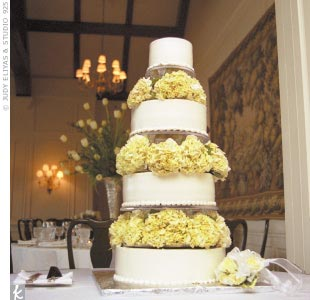 Pale green hydrangeas separated each tier of Holly and Harry's wedding cake, with four tiers of yellow chiffon filled with chocolate mousse and fresh raspberries.