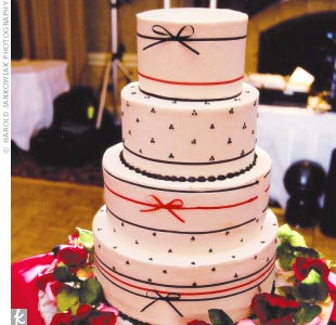Stephanie and Nick's white, four-tier cake was iced in vanilla buttercream and accented with Swiss dots and ribbons.