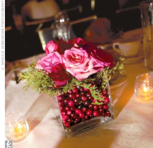 Red roses, in square vases lined with cranberries, adorned tables topped with ivory and red linens at Stephanie and Nick's reception.