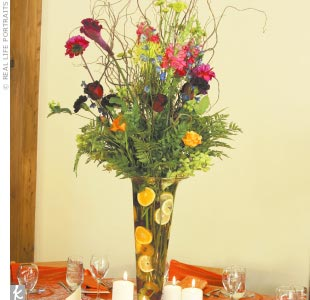 Colorful centerpieces overflowing with flowers and fresh fruit matched the different bridesmaid dresses.
