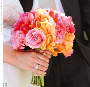 Roses and orchids in complementary shades of amber, coral, and apricot brightened the bride's muted-tone gown.