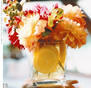The centerpieces at Amanda and Alex's wedding reception consisted of square glass vases filled with dahlias, hypericum berries, and sliced lemons.