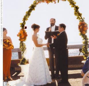 "Amanda and Alex were married overlooking the water under a large arbor covered with red, yellow, and orange dahlias (the bride's favorite flower), which matched the bridesmaid bouquets. ""Right as we were finishing our vows, the arbor toppled over,"" says Amanda, who couldn't have cared less as it further opened up a view to their guests of the great ..."