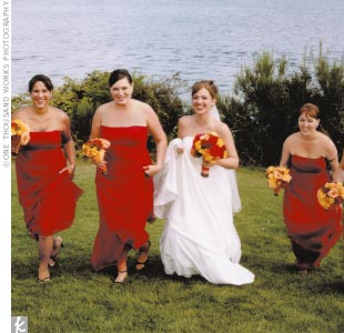 Amanda's bridesmaids donned strapless chiffon empire-waist gowns in a rich red color by After Six. They also carried red, yellow, and orange bouquets.