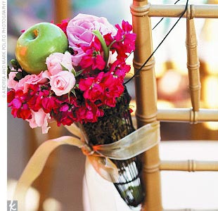 Iron cones covered with moss, baby apples, roses, hydrangea, and gold organza ribbon hung at the end of each row of gold chiavari chairs.