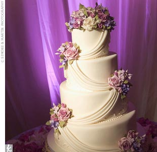 The three-tiered confection was classically iced in white fondant with a swag effect while handmade fondant florals in lavender decorated each layer.