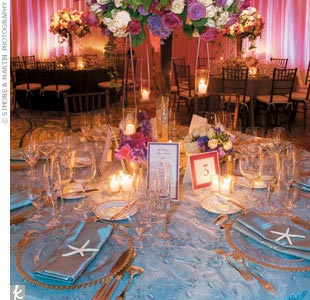 Inside the ballroom, soft ambient lighting enhanced the fabric-draped walls in lavender and purple tones. At each table, floral arrangements popped out from tall silver trumpet vases strung with clear votives that hung from platinum ribbons.