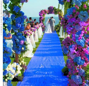 The beautiful two-post and four-post ceremony arches placed at opposite ends of the aisle were overflowing with vibrant blue hydrangeas; lavender, purple, and white roses; hanging amaranthus; and cymbidium orchids.