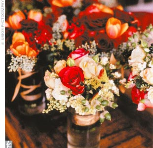 Tables were covered with sheer sage green overlays and topped with low centerpiece arrangements of dahlias, roses, tulips, berries, and foliage.