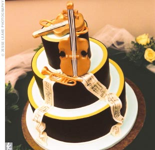 Julie Durkee designed a three-tier cake with musical instruments on the top and scrolls of sheet music running down the sides. The cake featured three flavors: vanilla cake with raspberry and mascarpone filling, chocolate cake with hazelnut cream filling, and carrot cake. The grooms cake, chocolate cake with raspberry filling, was made in the shap ...