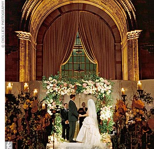 Lori and Olie married at Cipriani 42nd Street, in the historic former Bowery Savings Bank, now converted into a reception hall, complete with lofty ceilings and marble columns. Since much of the space has been preserved, the couple was able to exchange vows in the original teller booths.
