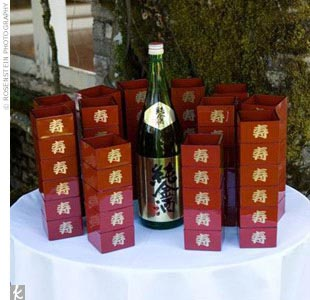 "In honor of the bride's mother's background, a traditional Japanese sake toasting ceremony (called san-san-kudo) was performed. ""The sake itself was special wedding sake that actually had flecks of real gold in the liquor,"" says Kimberly. In the meantime, guests were handed red lacquered cups embossed with a gold Japanese wedding symbol for a congr ..."