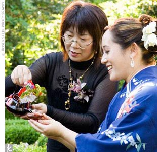 "For the san-san-kudo ceremony, Kimberly wore a formal indigo and white Japanese silk kimono embroidered with pink peonies and other flowers. To get the bride ready for her day, Kimberly enlisted her family: ""My cousin Akiko had taken special kimono dressing classes and my other cousin, Yoko, assisted her,"" she says"